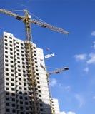 Кран и здание под конструкцией против голубого неба Стоковое Изображение