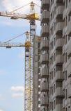 Кран и здание под конструкцией против голубого неба Стоковые Фотографии RF