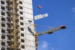 Кран и здание под конструкцией против голубого неба Стоковые Изображения