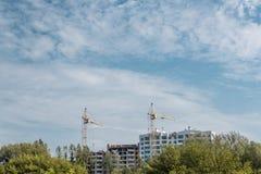 Кран и здание под конструкцией против голубого облачного неба стоковые изображения
