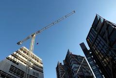 Кран и здания против голубого неба Стоковое фото RF