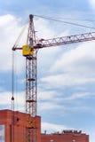 Кран конструкции башни против дома кирпича под constructio Стоковое фото RF