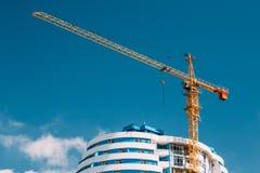 Кран конструкции включается в конструкцию нового жилого дома Мульти-этажа лето дня солнечное Стоковая Фотография