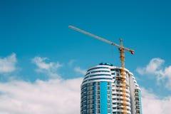 Кран конструкции включается в конструкцию нового жилого дома Мульти-этажа лето дня солнечное Стоковое Фото