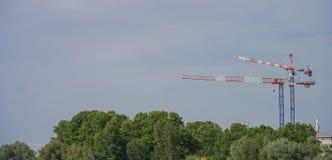 Кран конструкции возвышаясь над деревьями, городом и природой Стоковые Фотографии RF
