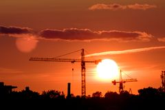 Кран конструкции на ландшафте города захода солнца Стоковые Изображения RF