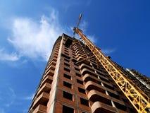 Кран конструкции около здания на предпосылке голубого неба Стоковые Фото