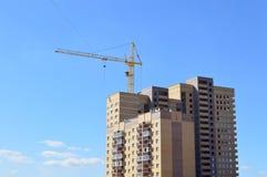 Кран конструкции около заново построенного блока квартир Стоковые Изображения