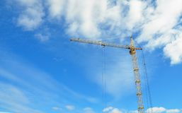 кран конструкции промышленный Большой кран конструкции и здание Желтый поднимая кран против cloudscape Стоковые Изображения