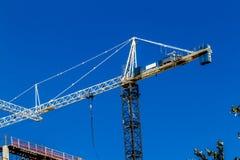 Кран на работе конструкции высотного здания опасность Стоковое Изображение RF