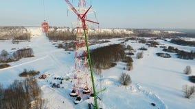 Кран поднимает вверх часть высокой башни против древесин зимы акции видеоматериалы