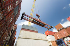 Кран понижая контейнер к стогу контейнеров Стоковая Фотография