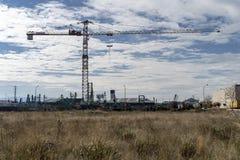 Кран против света в промышленном полигоне стоковая фотография