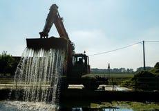 Кран экскаватора извлекает твердые частицы и водоросли строят вверх от канала Naviglio Pavese на солнечный день стоковая фотография rf