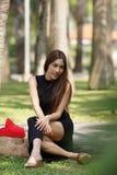 Красивая азиатская дама в черном платье, представляя в парке, более зеленом Стоковые Фото