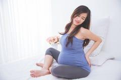 Красивая азиатская беременная женщина хмурясь пока держащ ее назад, стоковые изображения