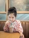 Красивая азиатская девушка выпивая замороженный шоколад в кафе Стоковая Фотография