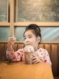 Красивая азиатская девушка выпивая замороженный шоколад в кафе Стоковое фото RF
