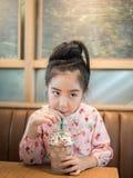 Красивая азиатская девушка выпивая замороженный шоколад в кафе Стоковое Изображение RF