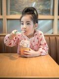 Красивая азиатская девушка выпивая замороженный шоколад в кафе Стоковые Фотографии RF