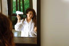 Красивая азиатская девушка в белизне суша ее волосы дома стоковое фото rf
