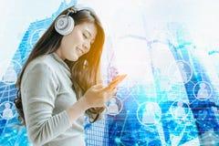 Красивая азиатская девушка работает на smartphone и слушает к m стоковые фото