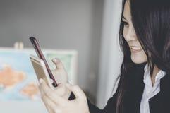 Красивая азиатская девушка усмехаясь счастливо, smartphones пользы аукционы онлайн, удобство концепций и скорость в цифровых поку стоковые фото