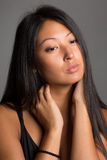 Красивая азиатская девушка на сером цвете Стоковое Изображение RF