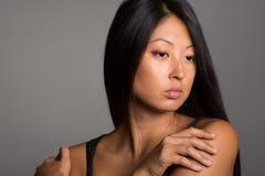 Красивая азиатская девушка на сером цвете Стоковое Фото