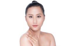 Красивая азиатская девушка штрихуя ее здоровую кожу изолированную на белизне стоковые фото