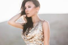 Красивая азиатская женщина в платье моды роскошном сияющем в пустыне стоковое фото