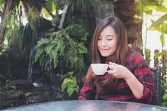 Красивая азиатская женщина держа белую кружку и выпивая горячий кофе с чувствовать счастливый в зеленом саде природы и водопада стоковое фото
