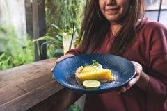 Красивая азиатская женщина держа и показывая желтый торт творога лимона с чувствовать счастливый и хороший образ жизни стоковые фото