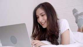 Красивая азиатская женщина играя компьютер или компьтер-книжку пока лежащ на кровати в ее спальне