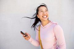 Красивая азиатская женщина идя снаружи с мобильным телефоном и усмехаться Стоковое Фото