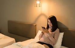 Красивая азиатская женщина используя смартфон на кровати вечером, заболевания глаза и концепция разладов глаз стоковое фото rf