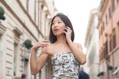 Красивая азиатская женщина используя внешнее весны мобильного телефона городское Стоковая Фотография RF