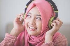 Красивая азиатская женщина наслаждаясь музыкой стоковое изображение