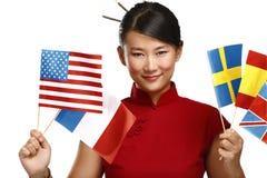 Красивая азиатская женщина показывая multicolor флаги international стоковое фото rf