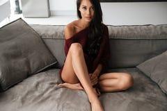 Красивая азиатская женщина при длинные волосы сидя на кресле Стоковое Фото