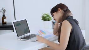 Красивая азиатская женщина работая и смотря данные по статистики анализа диаграммы диаграммы финансов со стрессом и серьезный на  акции видеоматериалы
