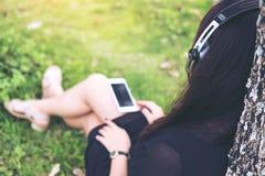 Красивая азиатская женщина сидя и слушая к музыке с наушниками и держа умный телефон деревом Стоковые Фото