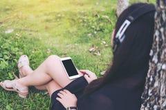Красивая азиатская женщина сидя и слушая к музыке с наушниками и держа умный телефон деревом Стоковые Изображения RF