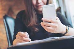 Красивая азиатская женщина с удерживанием и использованием стороны smiley умного телефона с кассетами на деревянном столе Стоковое Фото