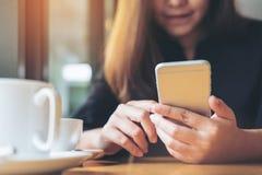 Красивая азиатская женщина с удерживанием и использованием стороны smiley умного телефона с кофейной чашкой на деревянном столе Стоковые Фотографии RF