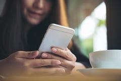 Красивая азиатская женщина с удерживанием и использованием стороны smiley умного телефона с кофейной чашкой на деревянном столе Стоковые Изображения