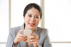 Красивая азиатская женщина усмехаясь и используя умное messagi текста телефона Стоковые Фотографии RF
