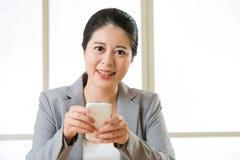 Красивая азиатская женщина усмехаясь и используя умное messagi текста телефона Стоковые Изображения RF