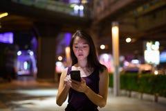 Красивая азиатская женщина outdoors на ноче используя мобильный телефон стоковое фото rf