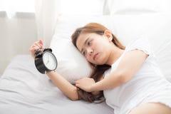 Красивая азиатская молодая женщина поворачивает будильник в добром утре, бодрствовании вверх для сна с будильником переднего план Стоковое Фото